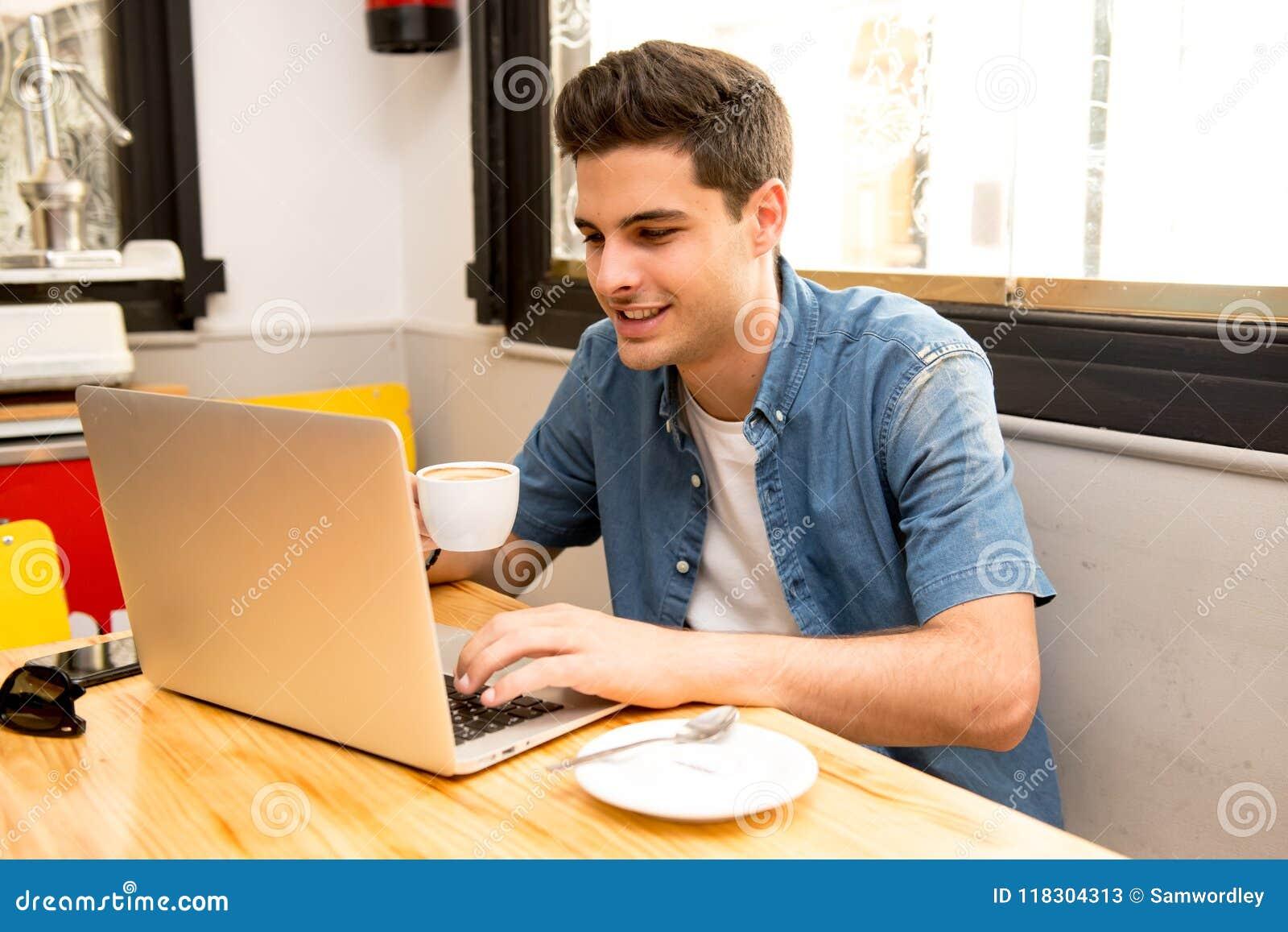 Νέο άτομο σπουδαστών που εργάζεται και που μελετά στον υπολογιστή στη καφετερία