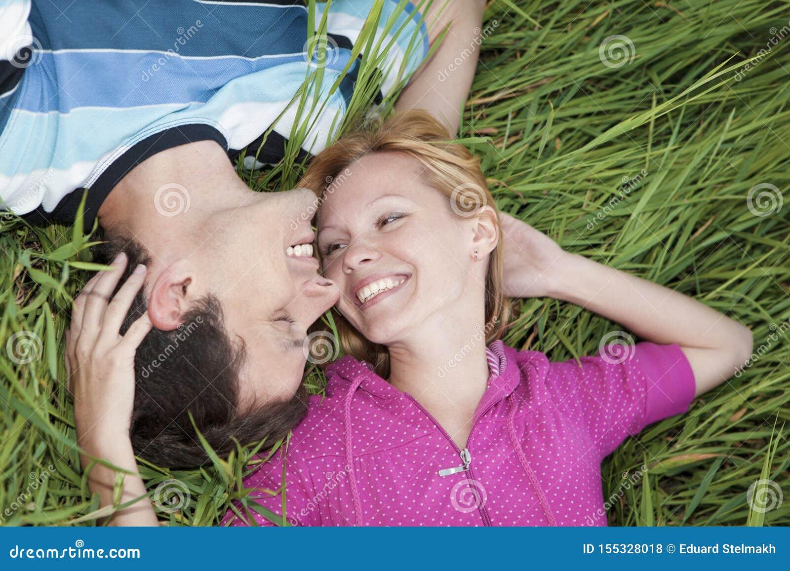 Νέο αγαπώντας ζεύγος που βρίσκεται στην πράσινη χλόη