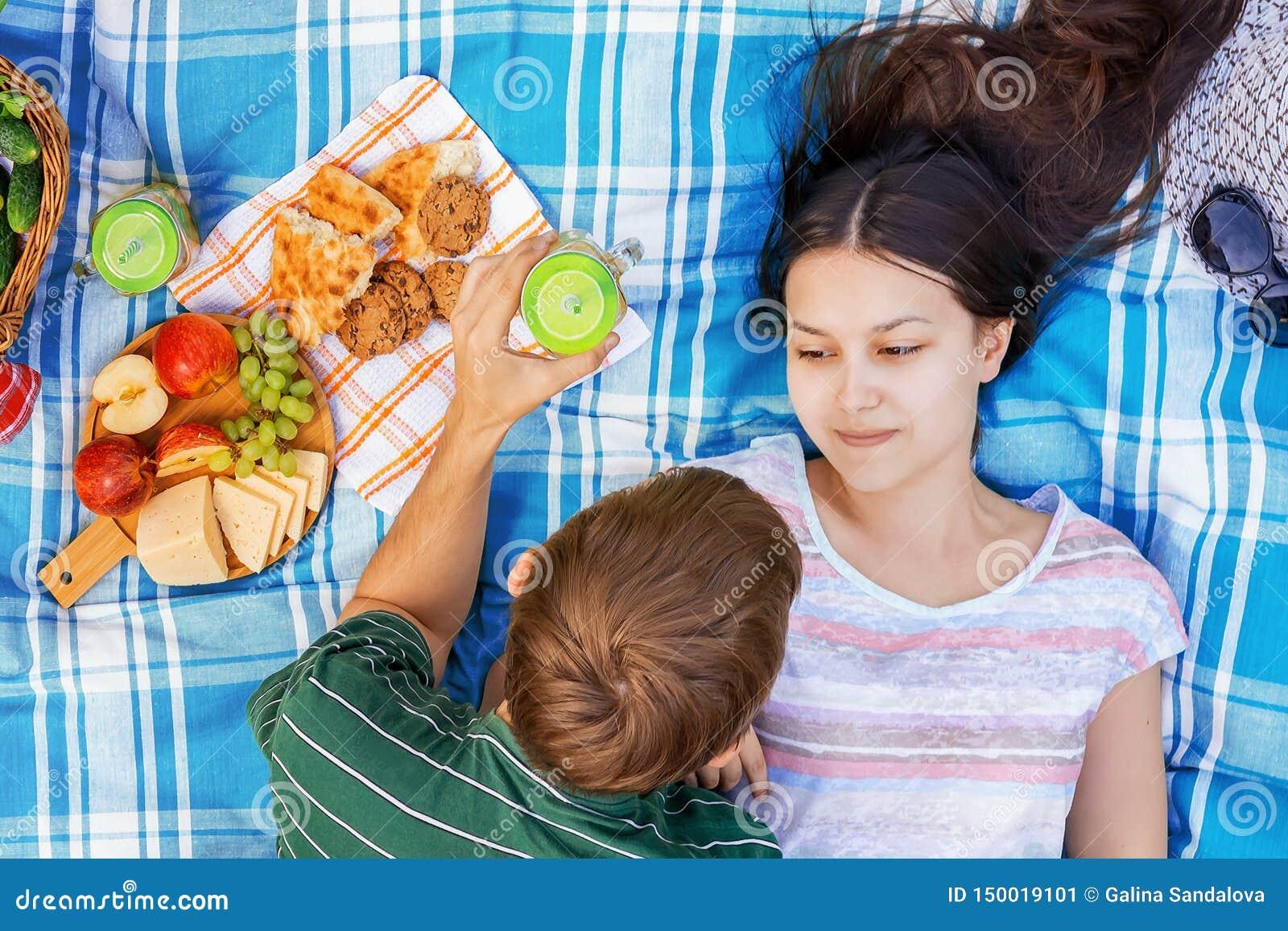 Νέο αγαπώντας ζεύγος που στηρίζεται σε ένα πικ-νίκ μια θερινή ημέρα