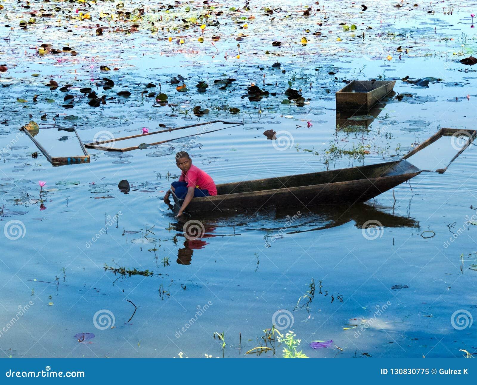 Νέο αγόρι σε μια βάρκα που μαδά το λουλούδι Lotus για τους τουρίστες