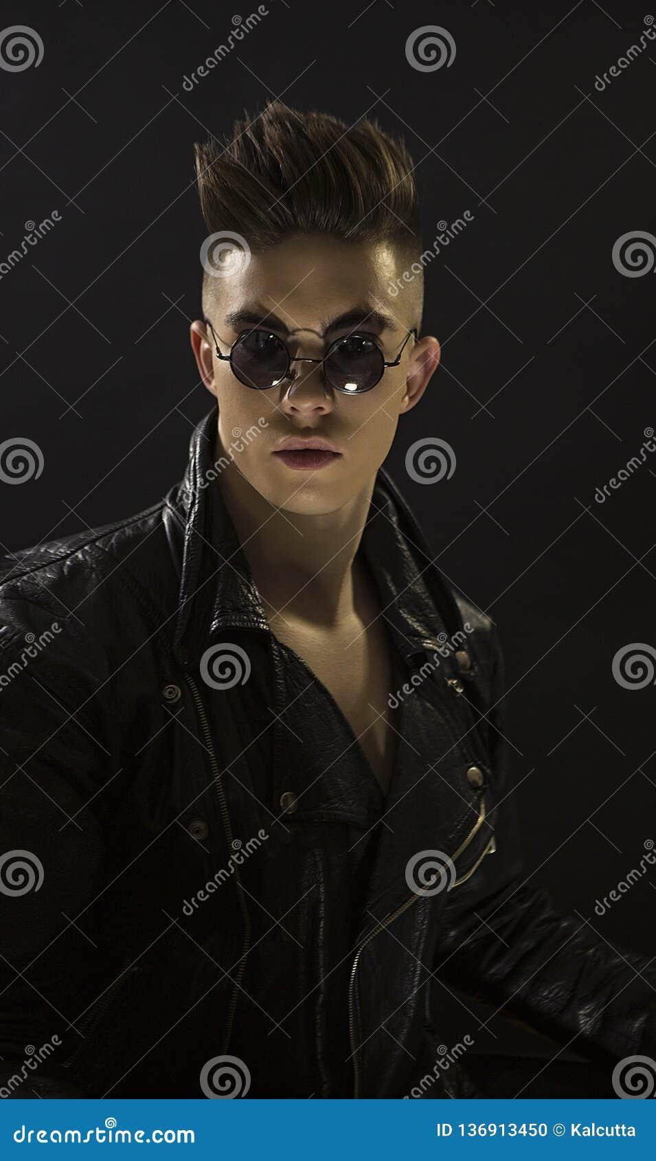 Νέο ανθρώπινο πορτρέτο με τα στρογγυλά γυαλιά ηλίου Μοντέρνο όμορφο προκλητικό αγόρι στο μαύρο σακάκι rocker-ύφους δέρματος μοντέ