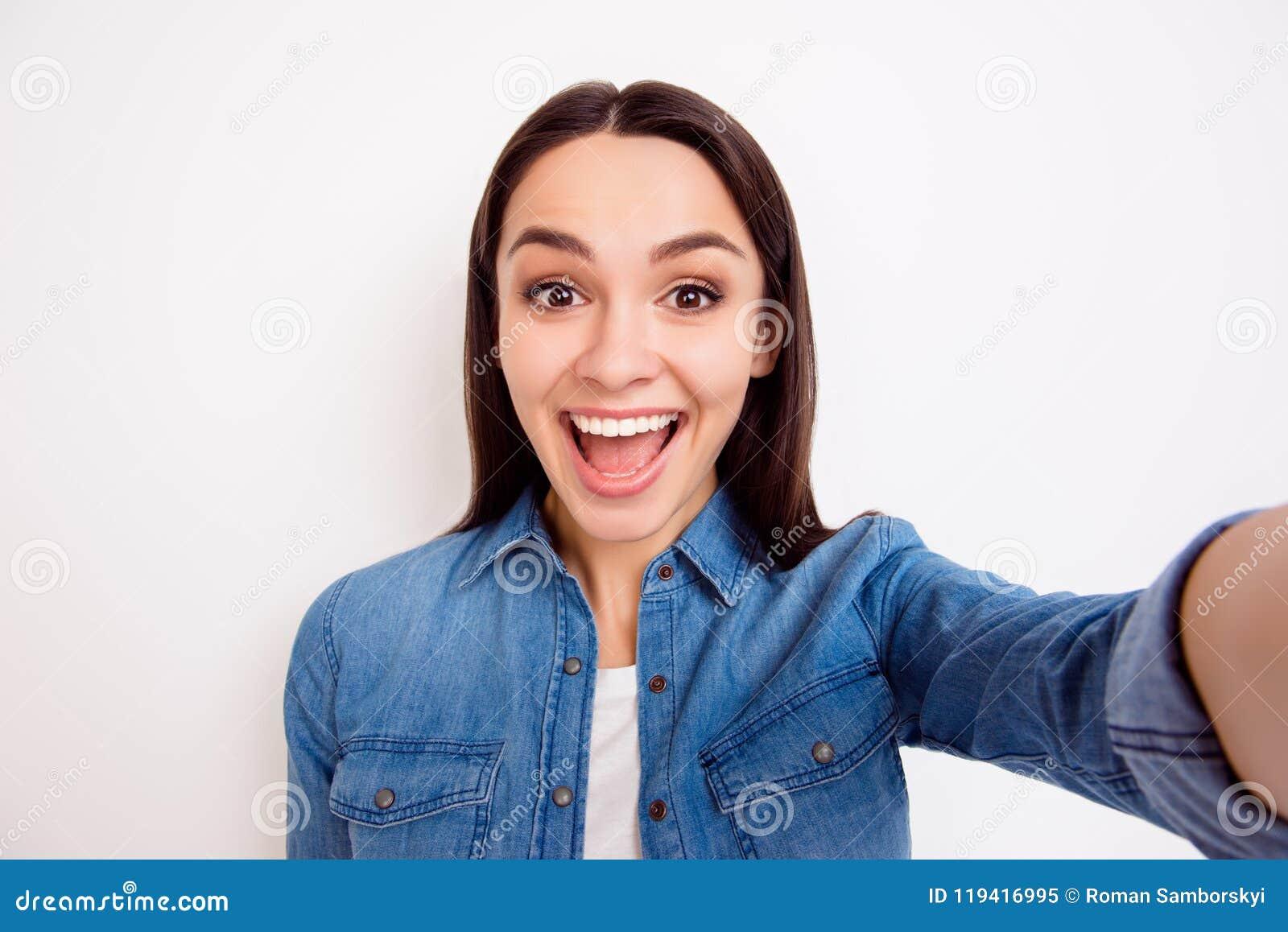 Νέο αρκετά εύθυμο κορίτσι στο πουκάμισο τζιν που παίρνει το μόνος-πορτρέτο