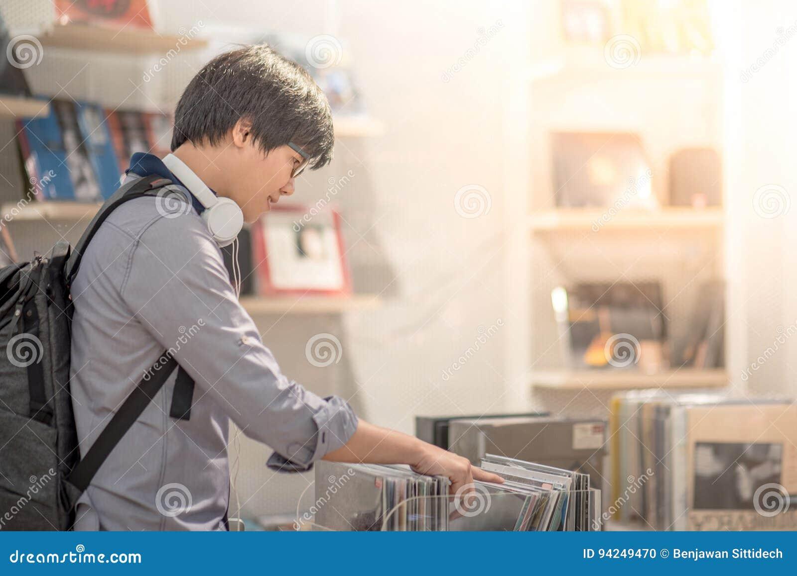 Νέο ασιατικό άτομο που επιλέγει το δίσκο στο κατάστημα μουσικής
