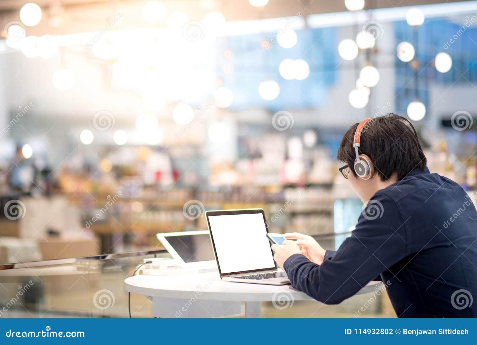 Νέο ασιατικό επιχειρησιακό άτομο που ακούει τη μουσική εργαζόμενο με το λ