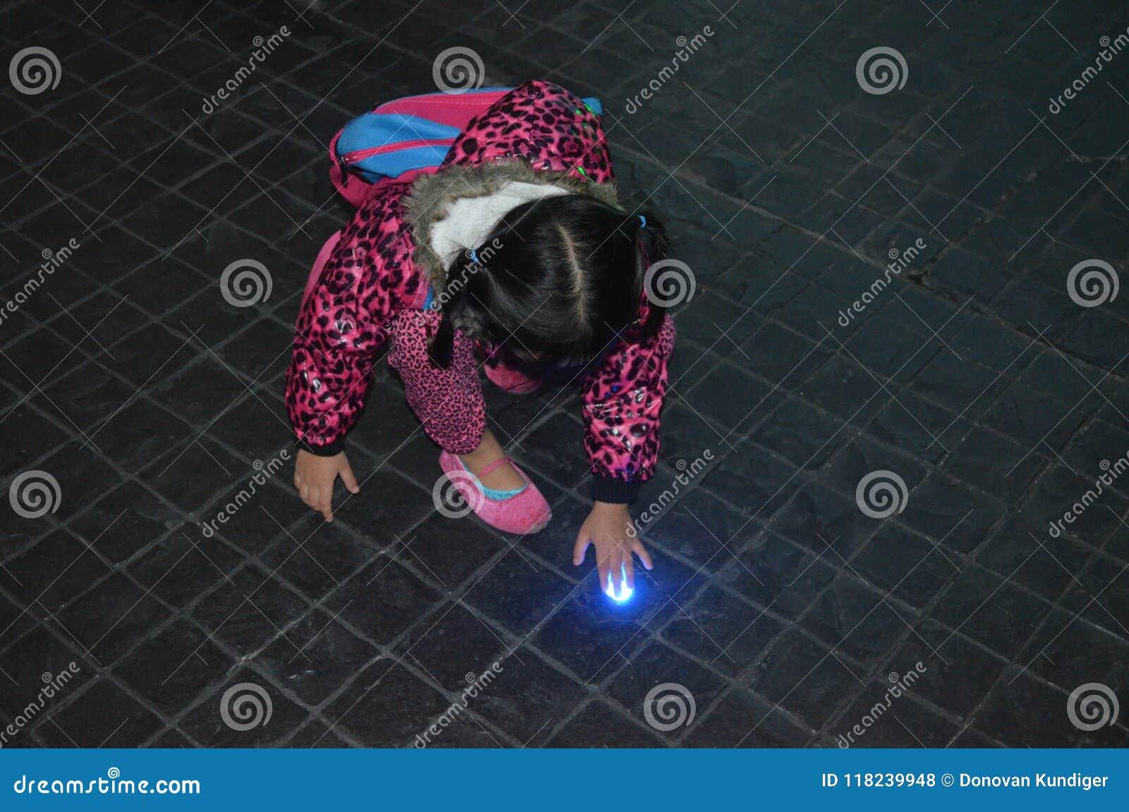 Νέο ασιατικό κορίτσι περίεργο για το φως στο πάτωμα