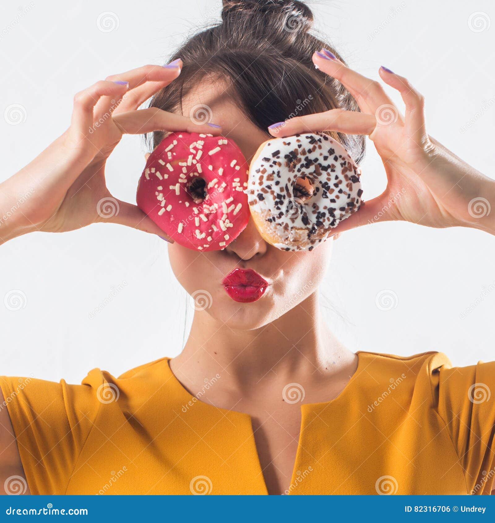 Νέο αστείο πρότυπο brunette με τα donuts που θέτουν το στούντιο που πυροβολείται υπόβαθρο, που δεν απομονώνεται στο άσπρο