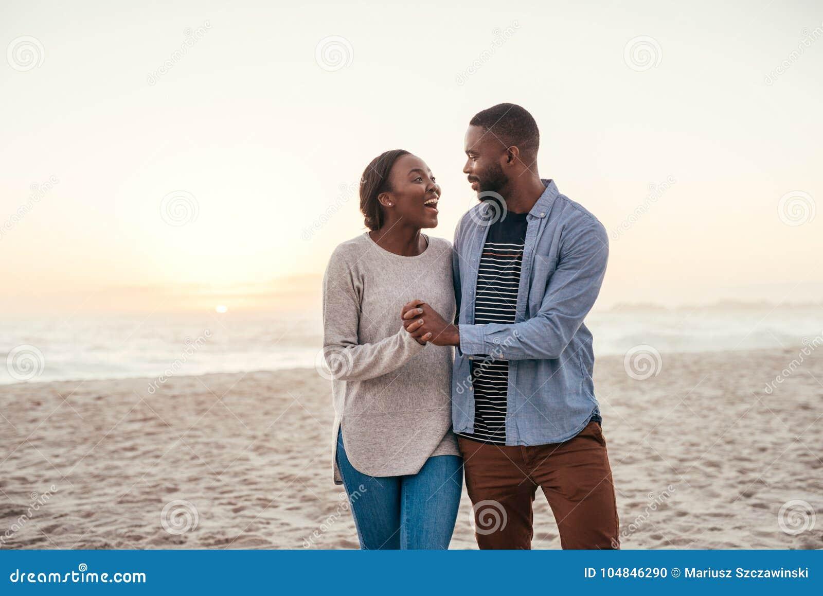Νέο αφρικανικό ζεύγος που περπατά σε μια παραλία στο γέλιο ηλιοβασιλέματος