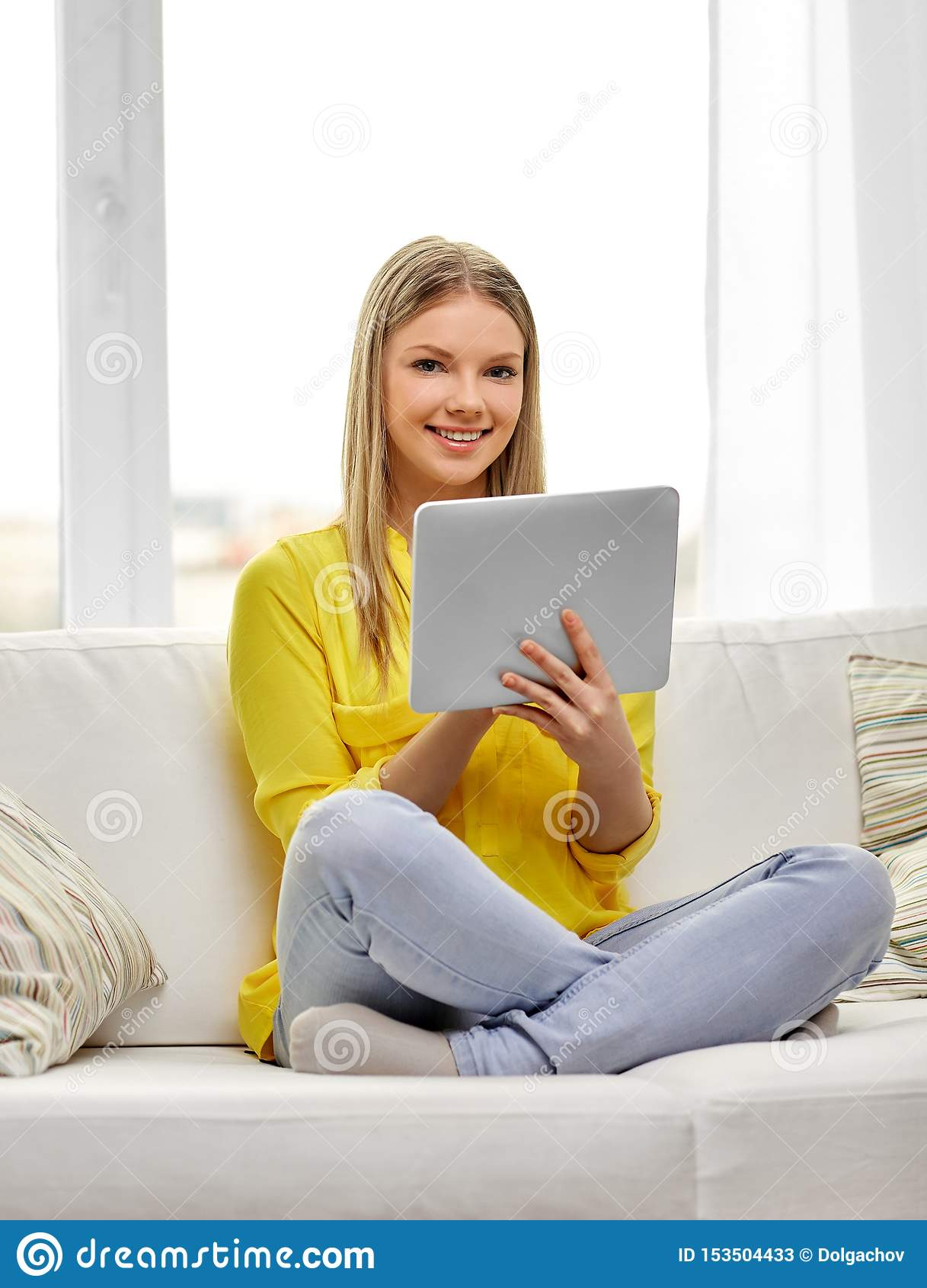 Νέο γυναίκα ή έφηβη με το PC ταμπλετών στο σπίτι