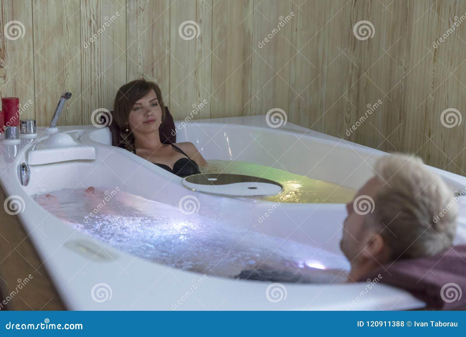 Νέο ευτυχές ζεύγος που απολαμβάνει το λουτρό στο τζακούζι - ζεύγος των εραστών σε μια λίμνη τζακούζι