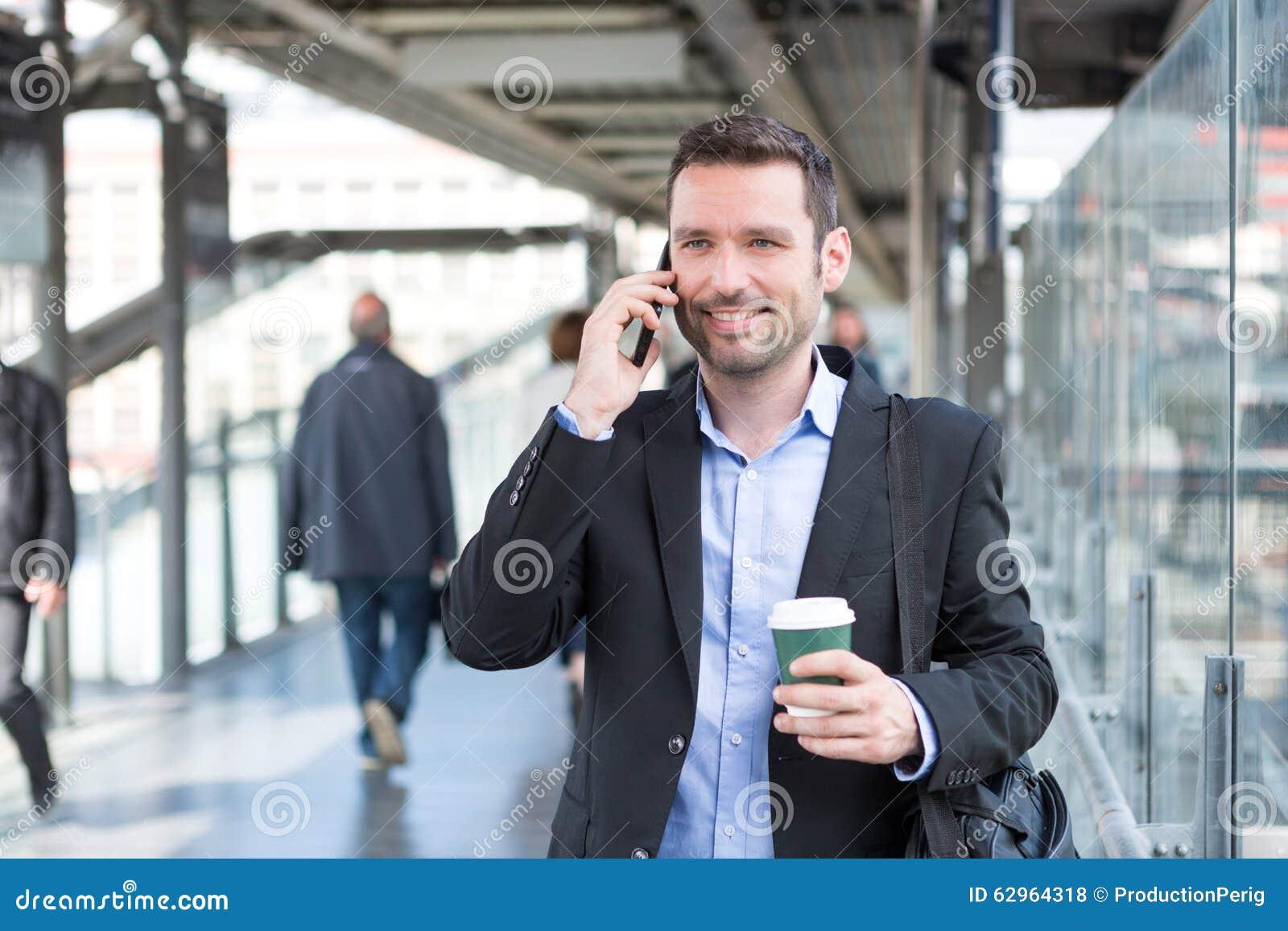 Νέο ελκυστικό επιχειρησιακό άτομο που χρησιμοποιεί το smartphone πίνοντας ομο