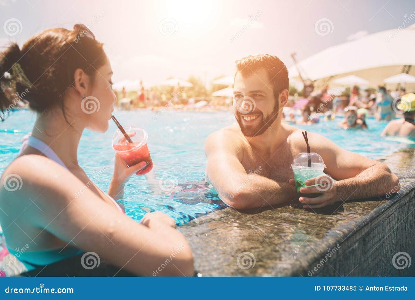 Νέο ζεύγος από την πισίνα Άνδρας και γυναίκες που πίνουν τα κοκτέιλ στο νερό