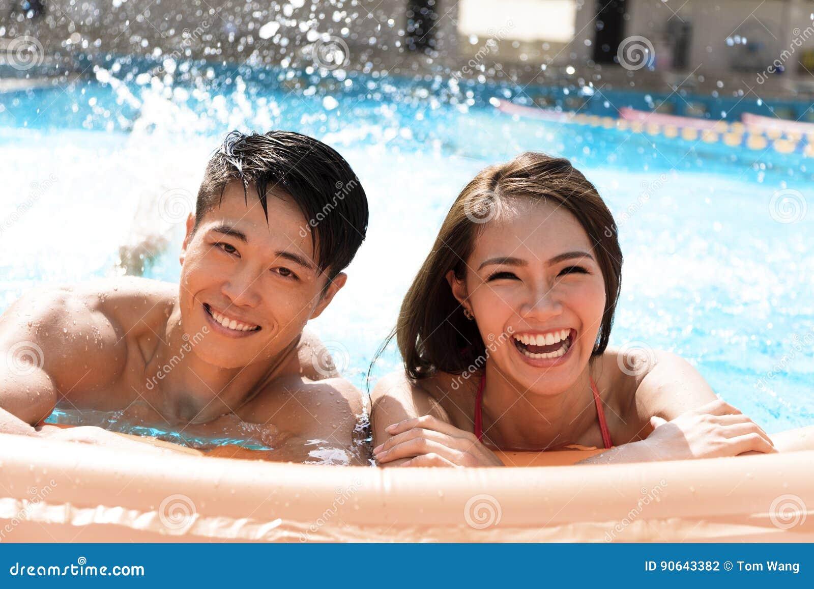 Νέο ζεύγος που έχει τη διασκέδαση στην πισίνα