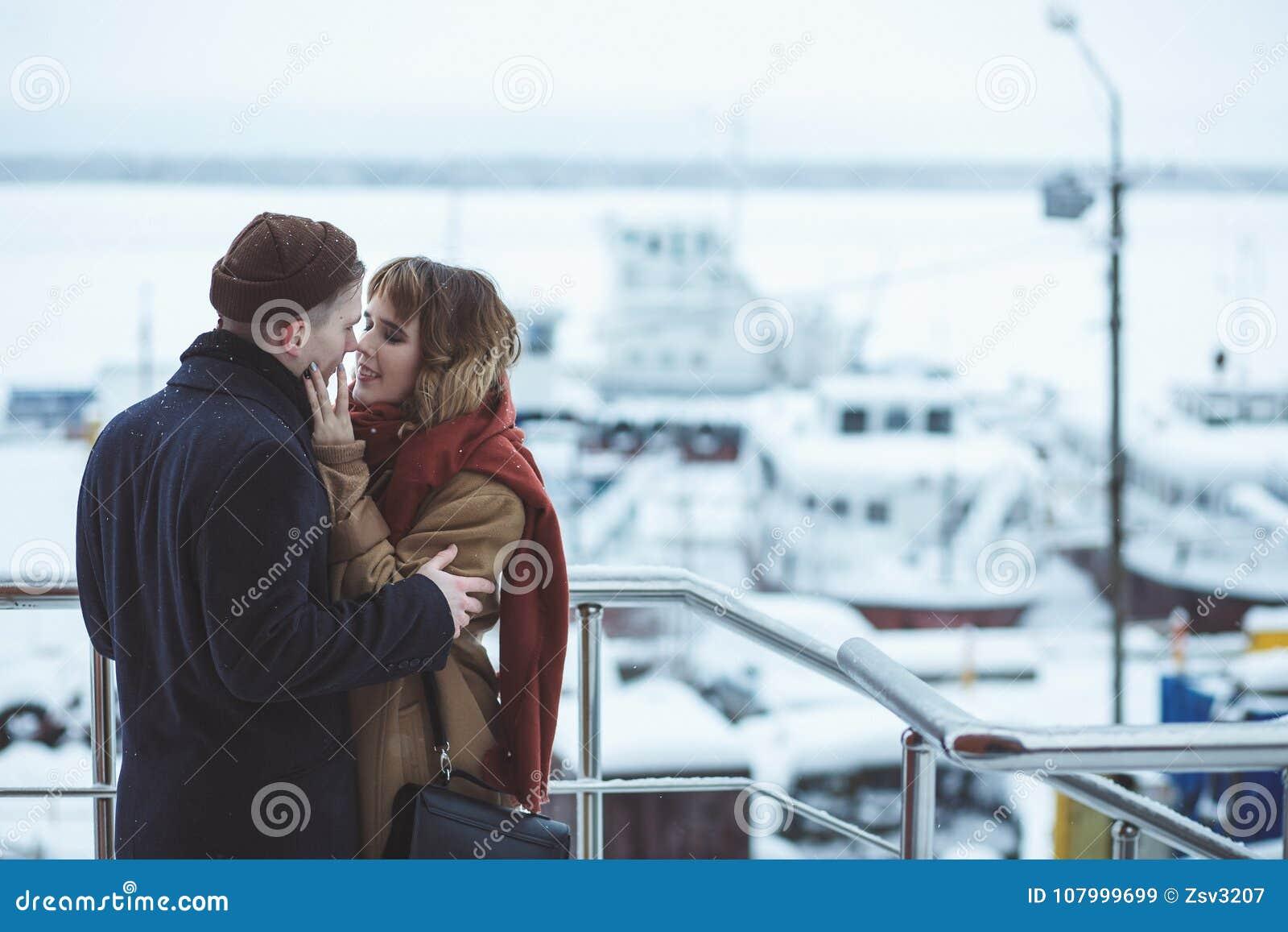 Νέο ζεύγος που αγκαλιάζει στη γέφυρα παρατήρησης στη χειμερινή πόλη Παγωμένα σκάφη στο bokeh