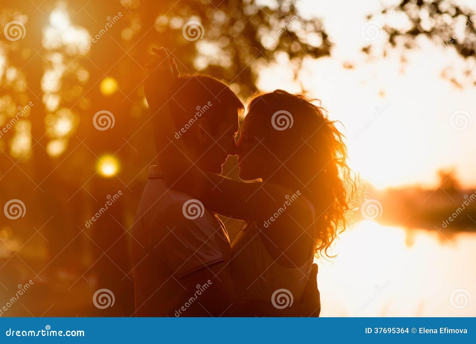 Νέο ζεύγος που αγκαλιάζει σε ένα άσπρο υπόβαθρο ενός ηλιοβασιλέματος