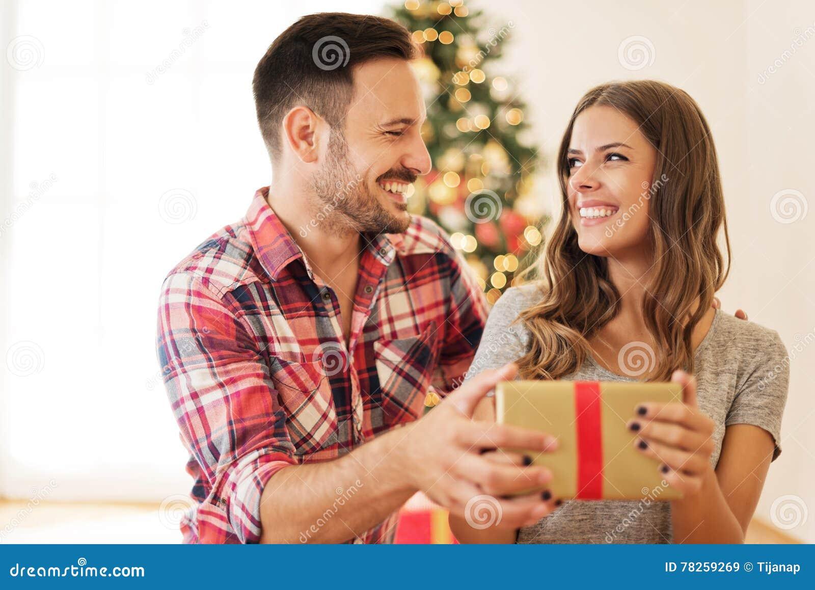 Νέο ζεύγος που ανοίγει ένα χριστουγεννιάτικο δώρο σε ένα πρωί Χριστουγέννων