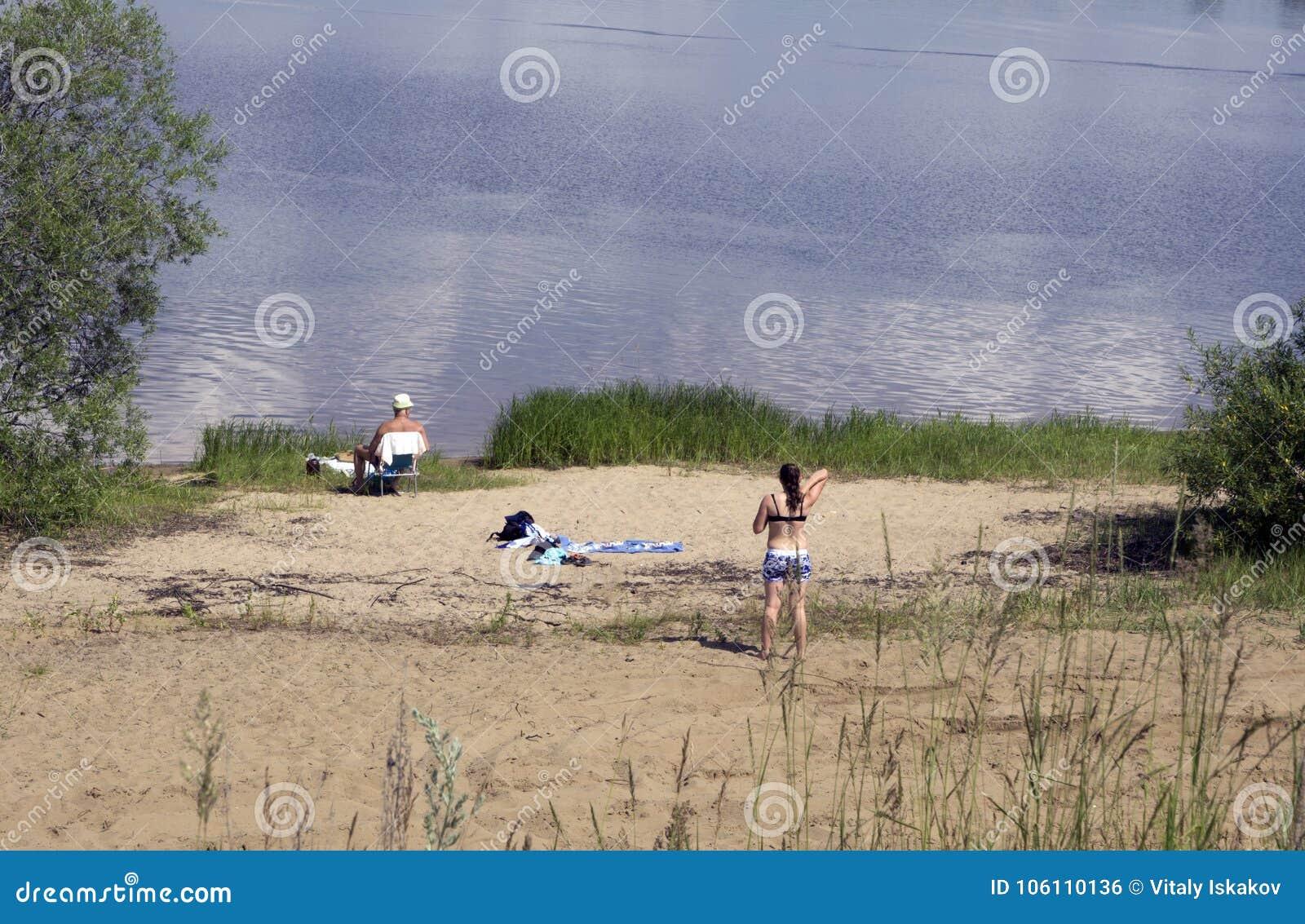Νέο ζεύγος που βάζει στην αμμώδη εν πλω ακτή παραλιών στην ηλιόλουστη ημέρα
