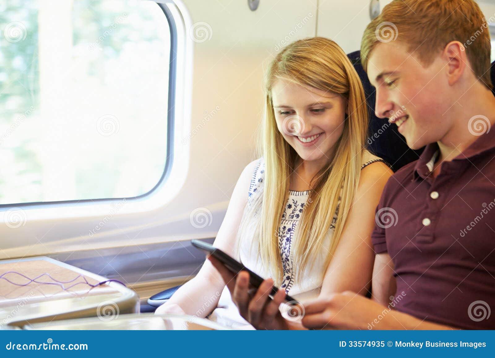 Νέο ζεύγος που διαβάζει ένα βιβλίο στο ταξίδι τραίνων