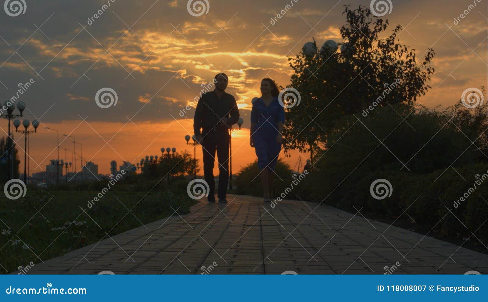 Νέο ζεύγος που περπατά στη κάμερα Ηλιοβασίλεμα
