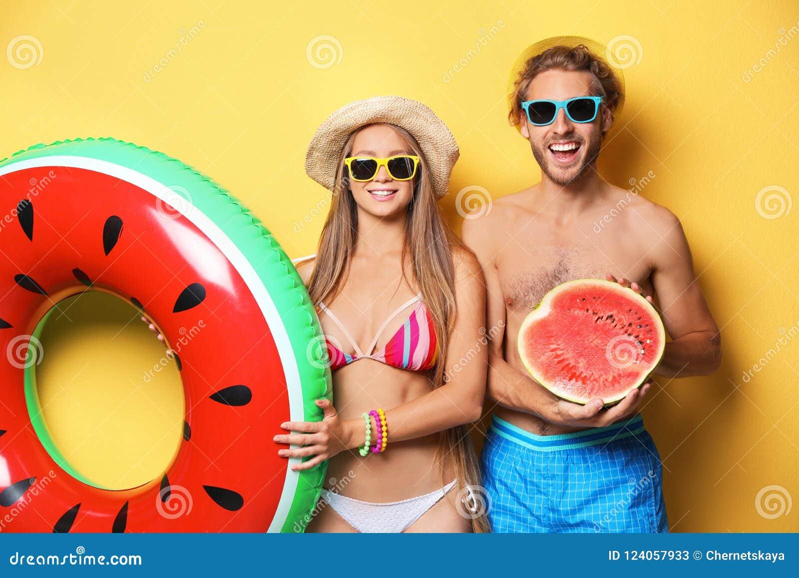 Νέο ζεύγος σε beachwear με το διογκώσιμα δαχτυλίδι και το καρπούζι