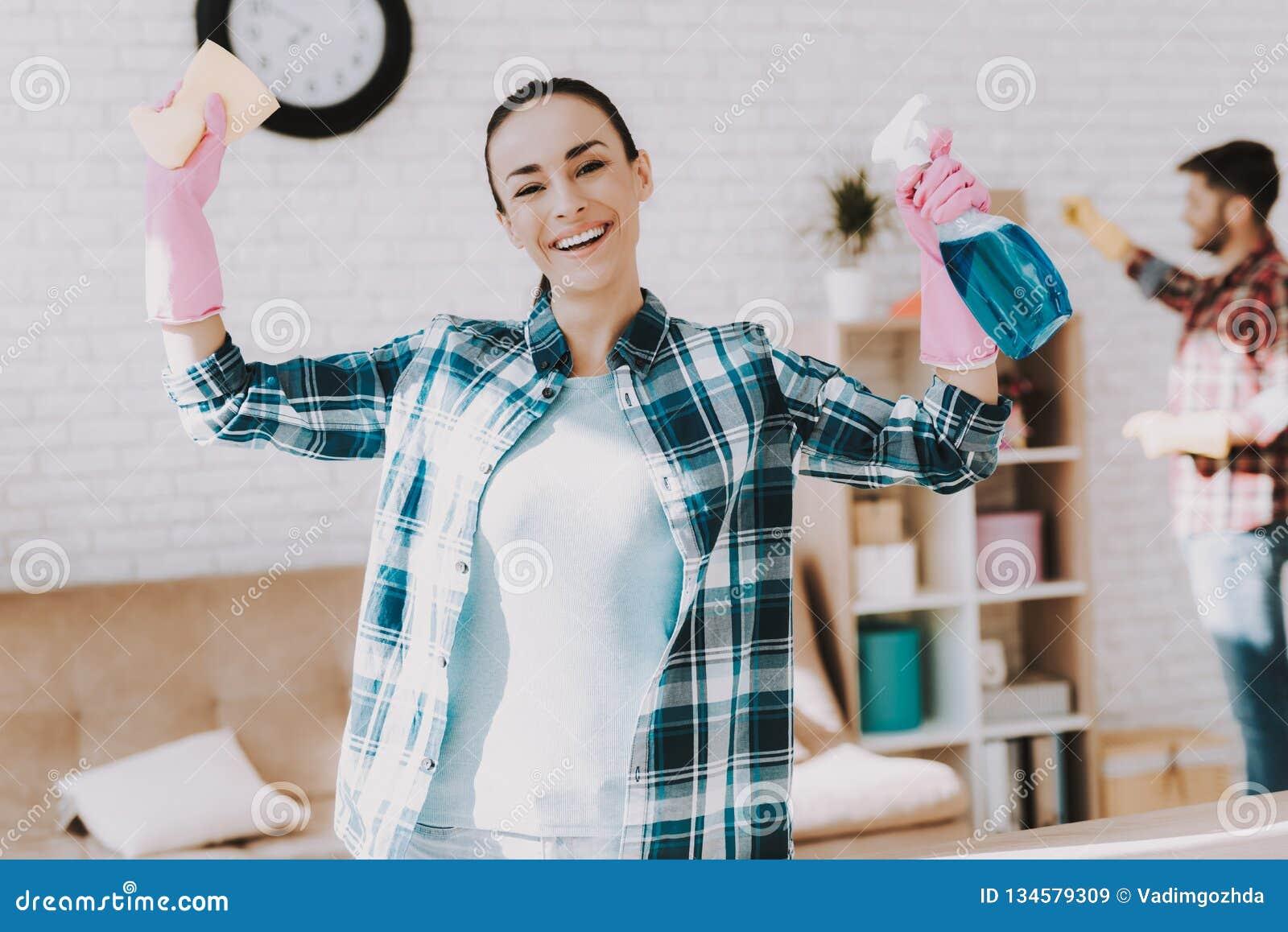 Νέο ζεύγος στα ελεγμένα πουκάμισα που καθαρίζουν το δωμάτιο