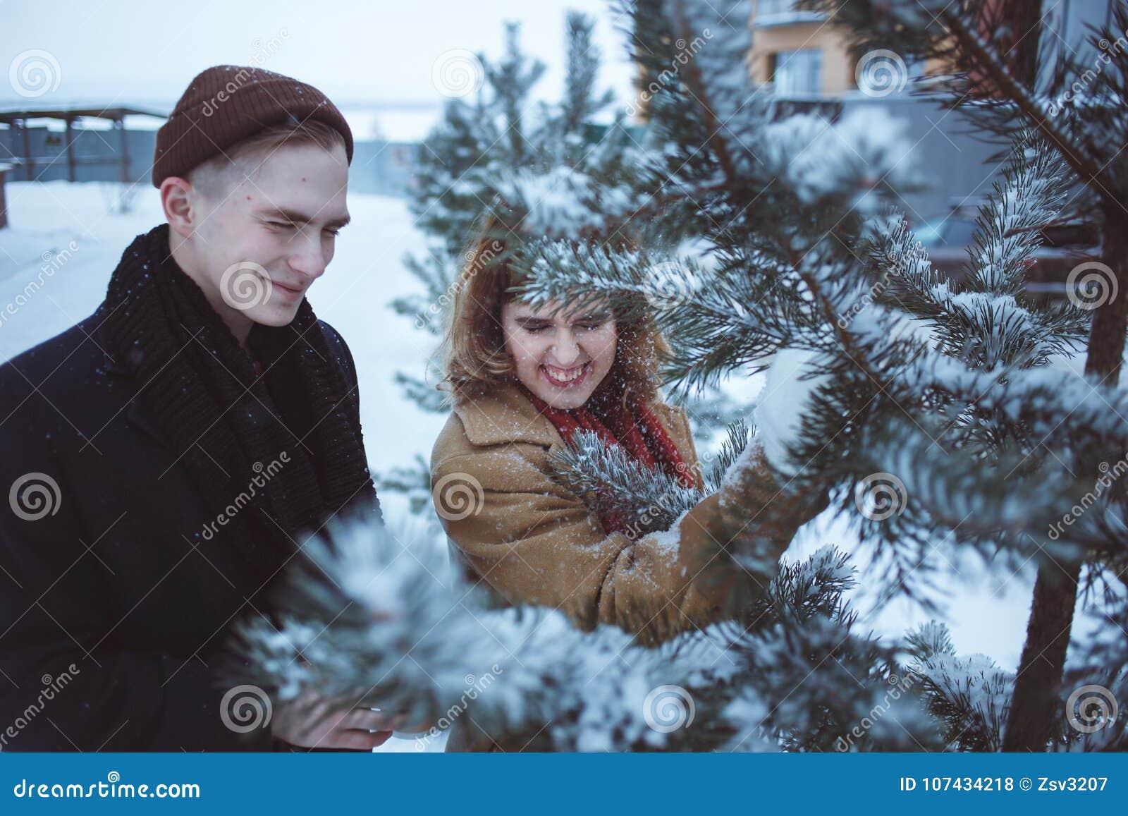 Νέο ζεύγος στο καλυμμένο κλάδοι χιόνι πεύκων Φίλη και φίλος που απολαμβάνουν τις ευτυχείς διακοπές ημέρας βαλεντίνων ` s στιγμών
