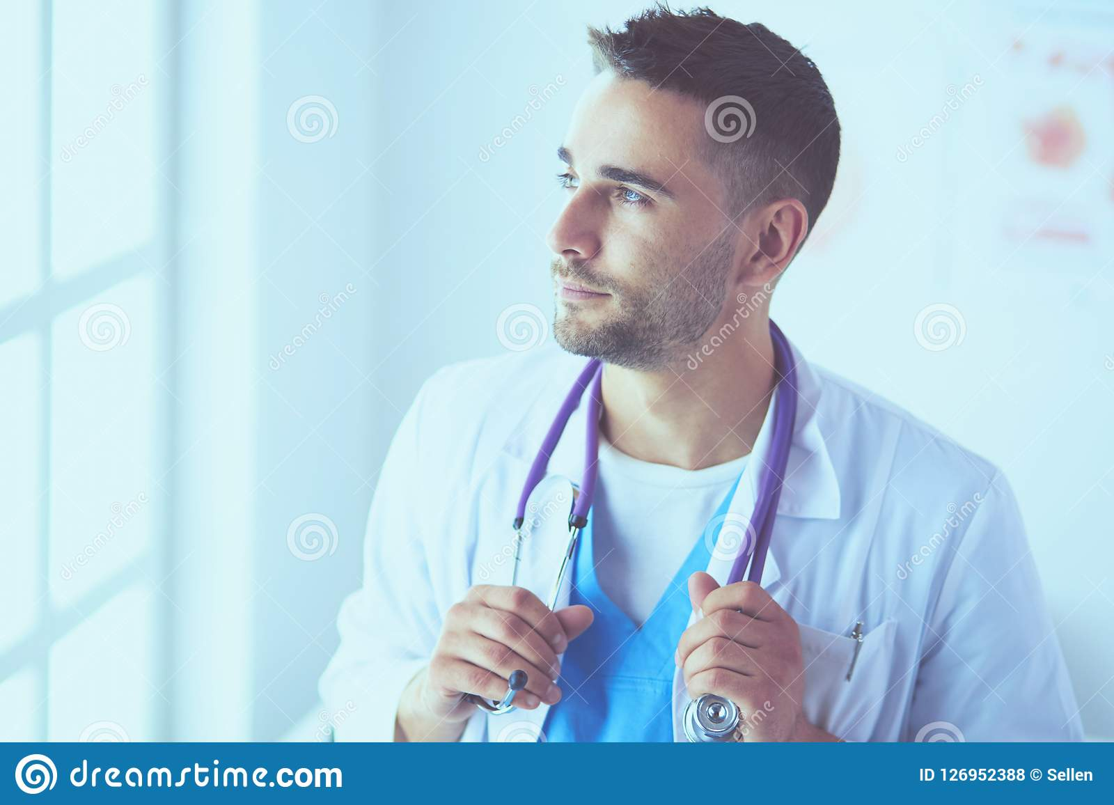 Νέο και βέβαιο αρσενικό πορτρέτο γιατρών που στέκεται στο ιατρικό γραφείο