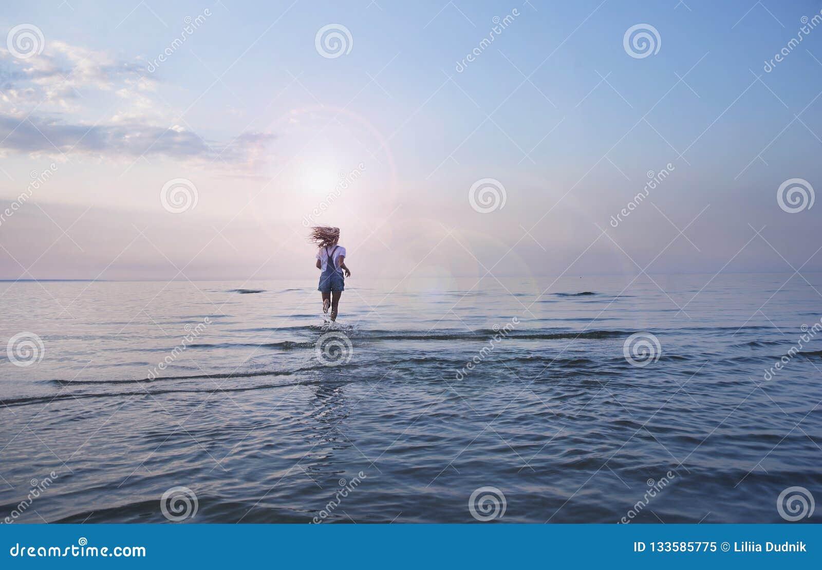 Νέο κατάλληλο γυναικών σε μια παραλία στο μπικίνι στο Μπαλί Τρέξιμο υπαίθριο ή επίλυση Κατάλληλη γυναίκα που τρέχει στην κενή ωκε