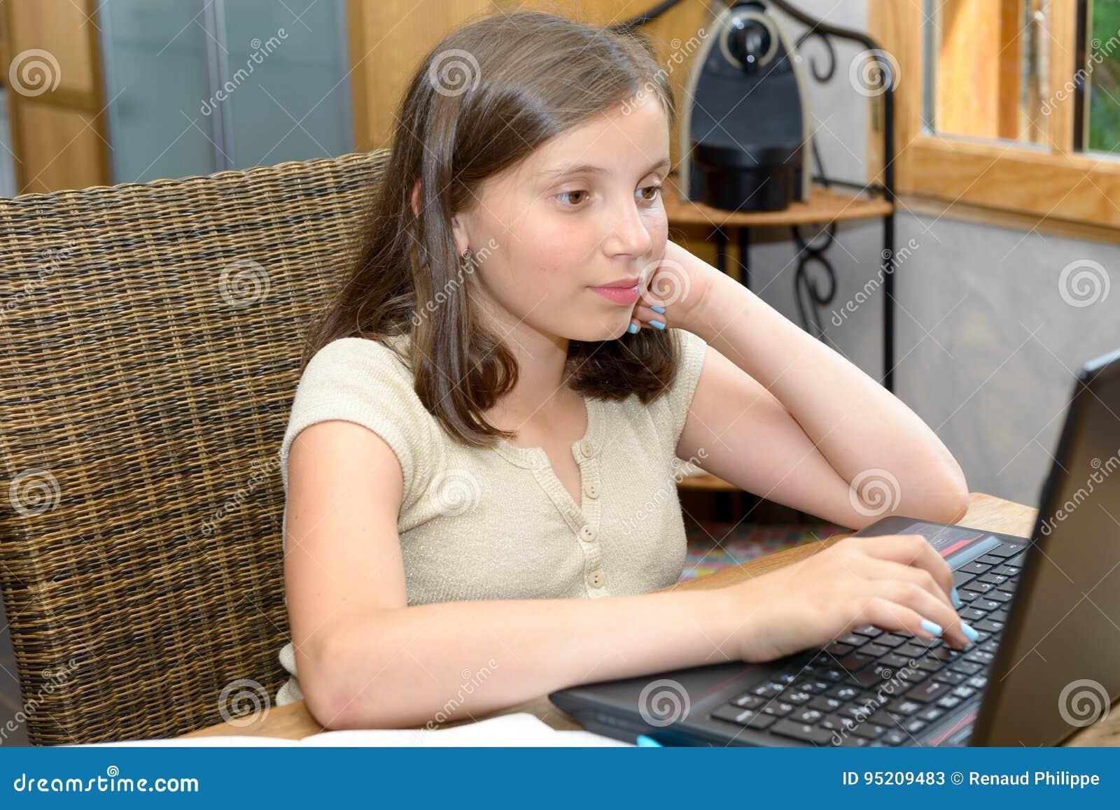 Νέο κορίτσι εφήβων που κάνει την εργασία της με το lap-top