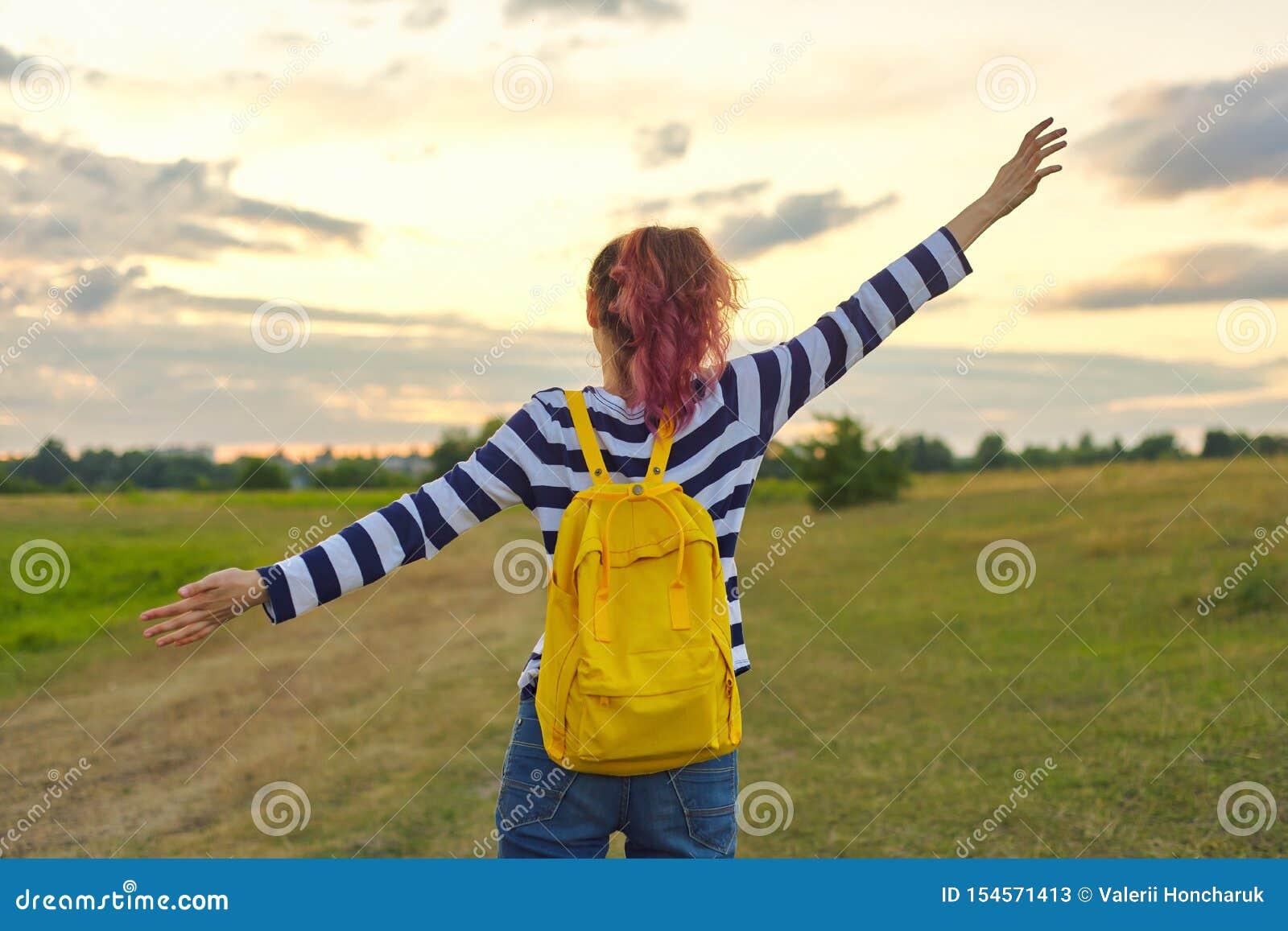 Νέο κορίτσι με το κίτρινο σακίδιο πλάτης, αυτή πίσω με τα ανοικτά χέρια