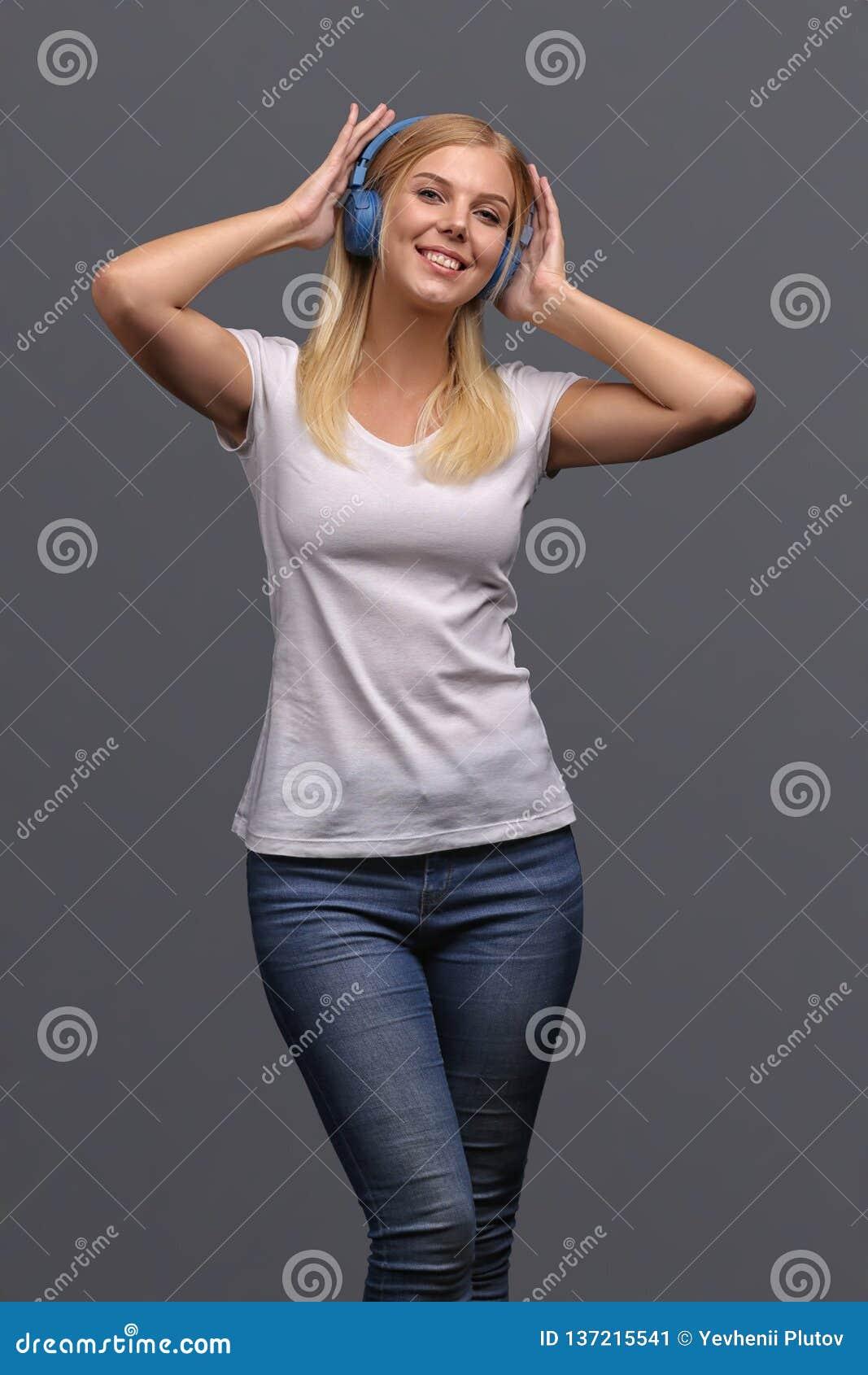 Νέο κορίτσι ξανθό στα μπλε ακουστικά Άκουσμα, που απολαμβάνει τη μουσική Απομονώστε σε ένα γκρίζο υπόβαθρο