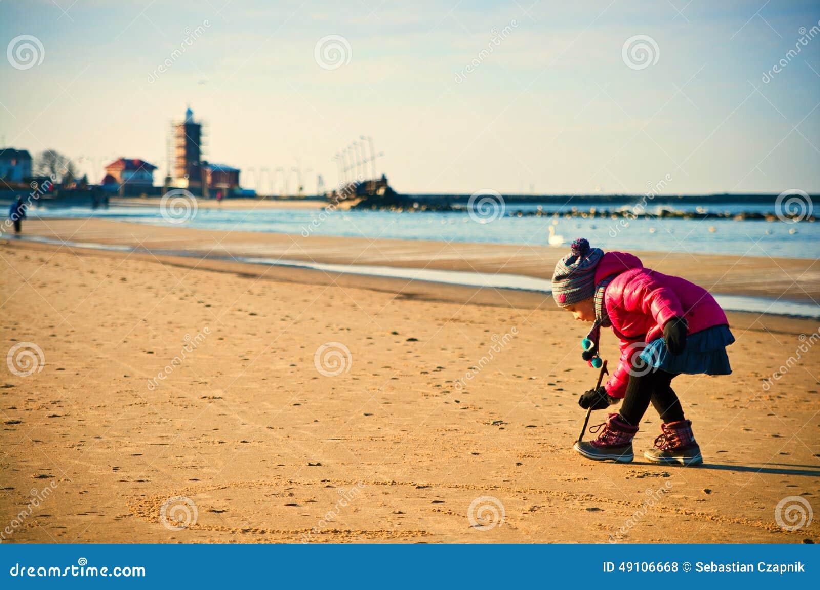 Νέο κορίτσι που έχει τη διασκέδαση στη χειμερινή βαλτική παραλία