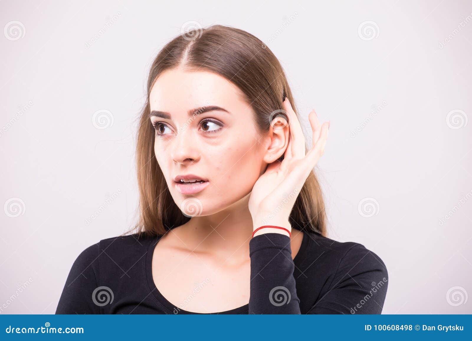 Νέο κορίτσι που ακούει με το χέρι της σε ένα αυτί