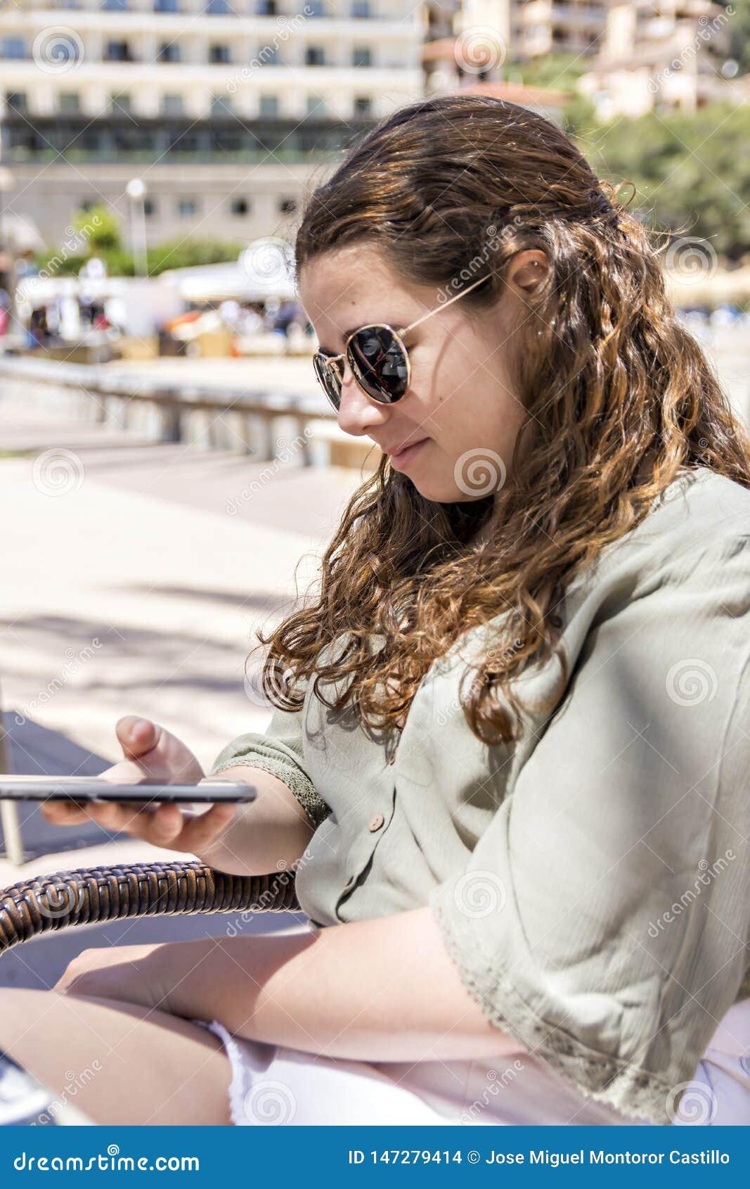 Νέο κορίτσι που εξετάζει το κινητό τηλέφωνο της μια ημέρα άνοιξη