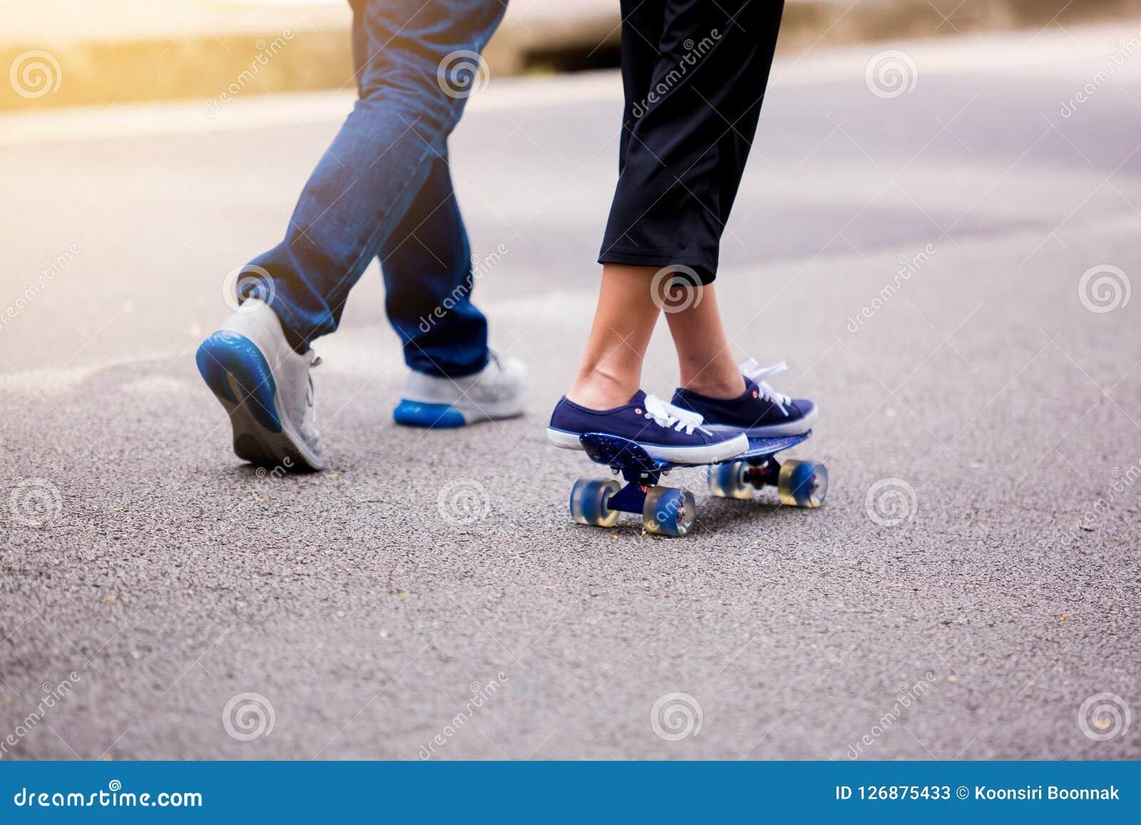Νέο κορίτσι που κάνει σκέιτ μπορντ με τον μπαμπά της που τρέχει στο πάρκο υπαίθριο ι