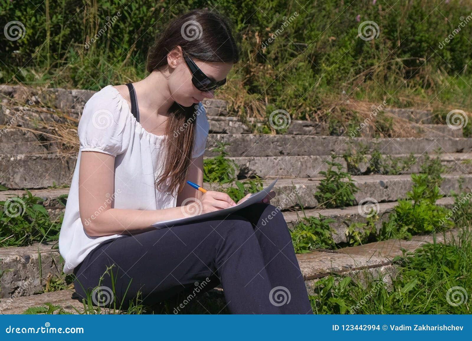 Νέο κορίτσι που κάνει τους στόχους και τη συνεδρίαση εργασίας της στο πάρκο Φοιτητής πανεπιστημίου