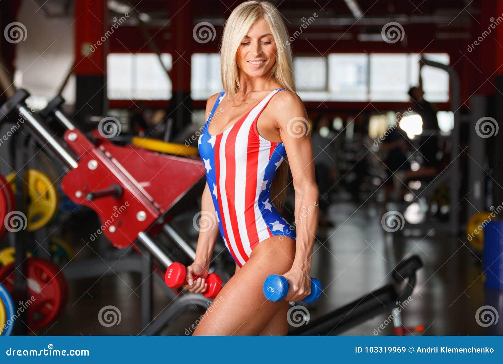 Νέο κορίτσι στάσεις στις φίλαθλες μπικινιών με έναν αλτήρα Μέσα στη γυμναστική
