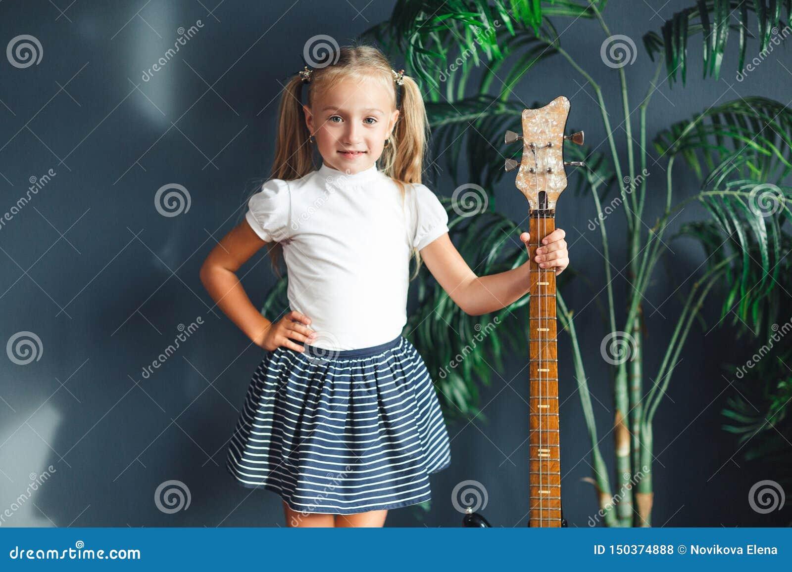 Νέο ξανθό κορίτσι με τις ουρές στην άσπρα μπλούζα, τη φούστα και τα σανδάλια με την ηλεκτρική κιθάρα που εξετάζει στο σπίτι τη κά