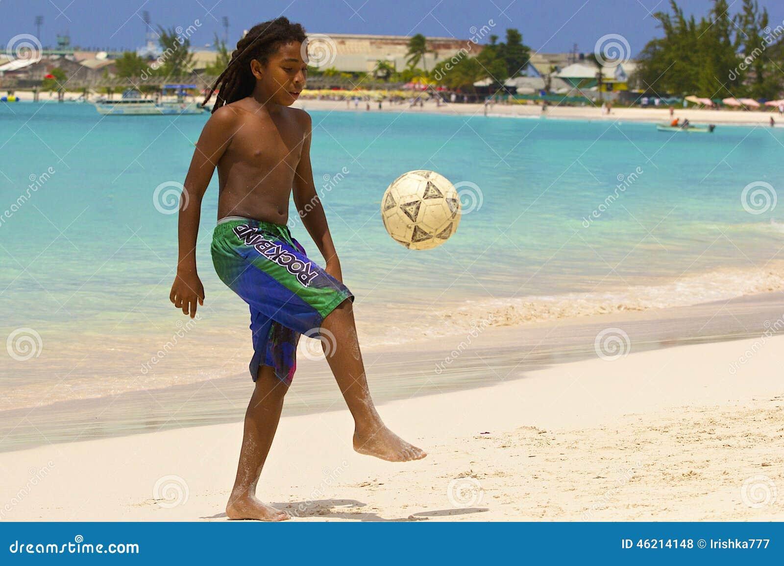 Νέο παίζοντας ποδόσφαιρο αγοριών στην παραλία στα Μπαρμπάντος, καραϊβικά