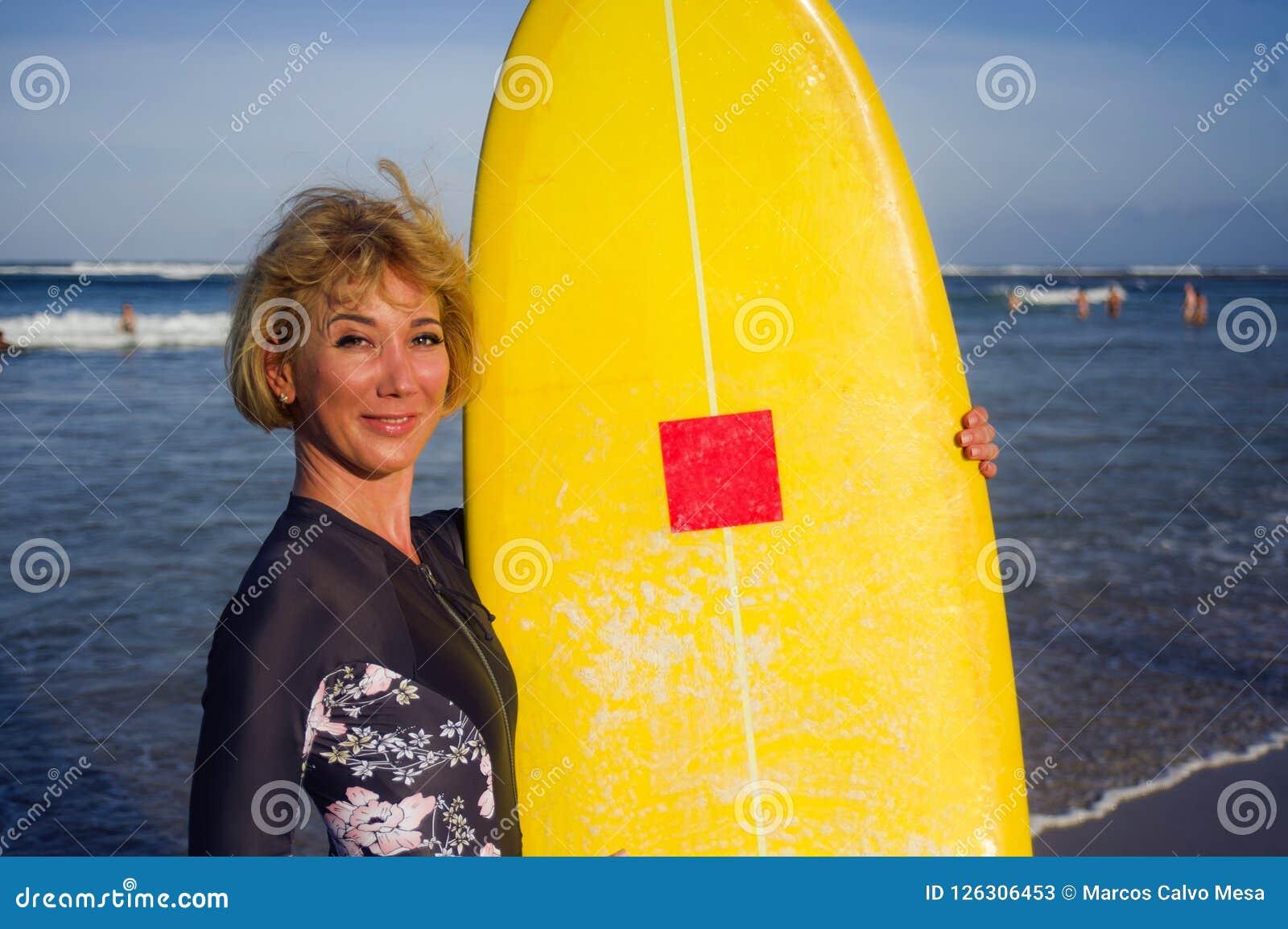 Νέο προκλητικό όμορφο και ευτυχές κορίτσι surfer που κρατά τον κίτρινο πίνακα κυματωγών που χαμογελά τις εύθυμες καλοκαιρινές δια