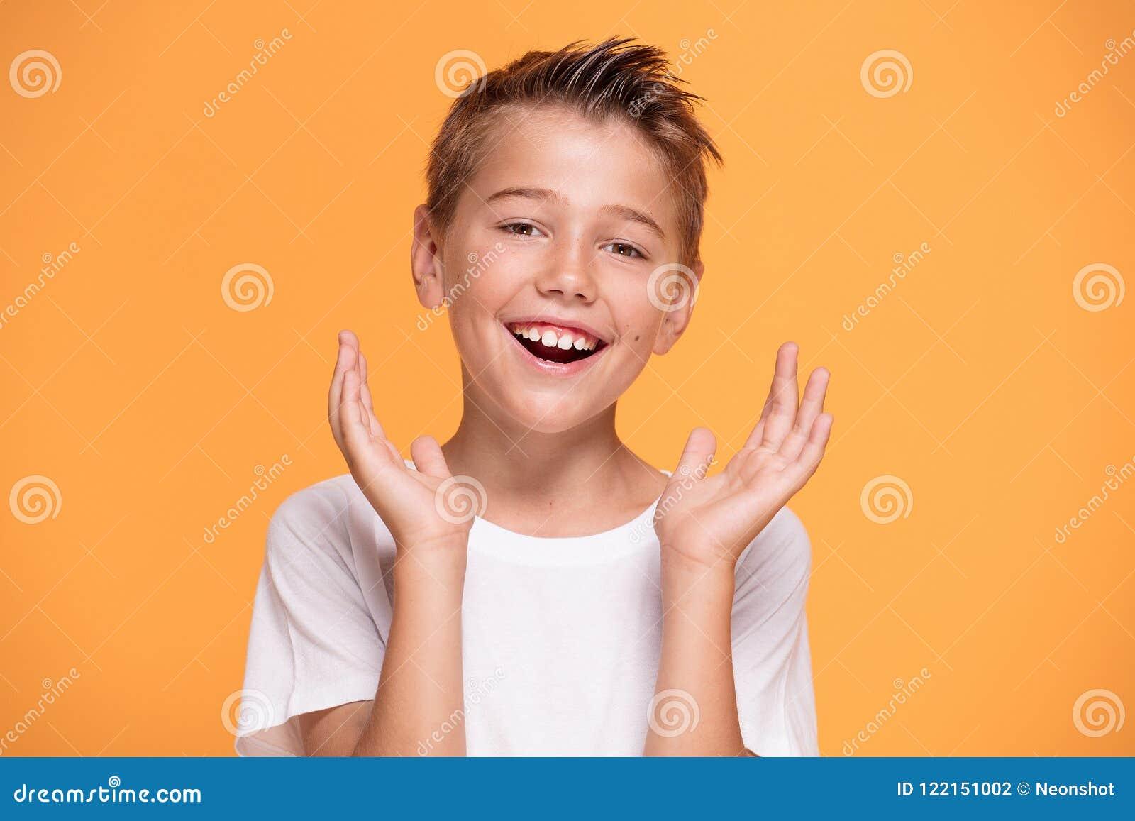 Νέο συναισθηματικό μικρό παιδί στο πορτοκαλί υπόβαθρο στούντιο