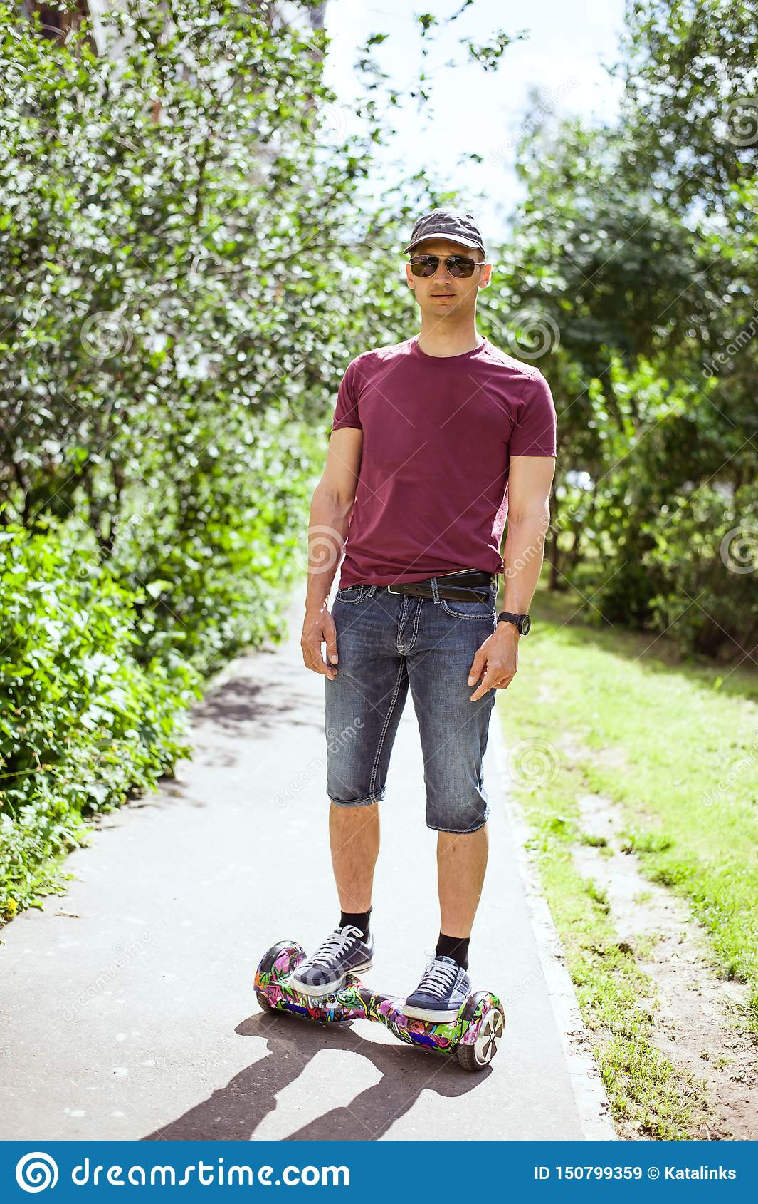 Νέο σύγχρονο άτομο στα σορτς τζιν και burgundy γύροι μπλουζών γύρω από την πόλη στο hoverboard