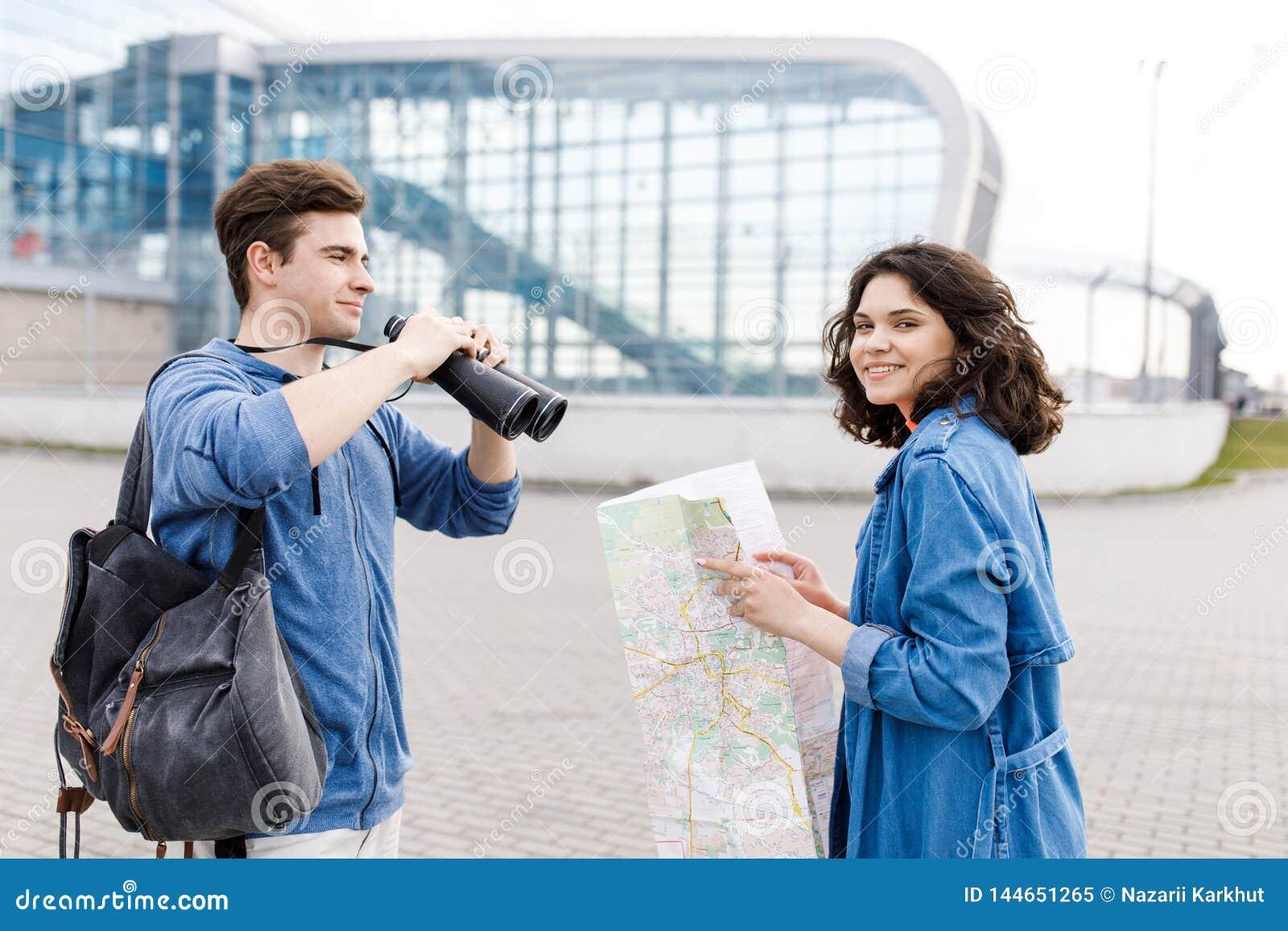 Νέο χαριτωμένο ζεύγος - ένα αγόρι και ένα κορίτσι που περπατούν γύρω από την πόλη με έναν χάρτη και τις διόπτρες στα χέρια του Οι