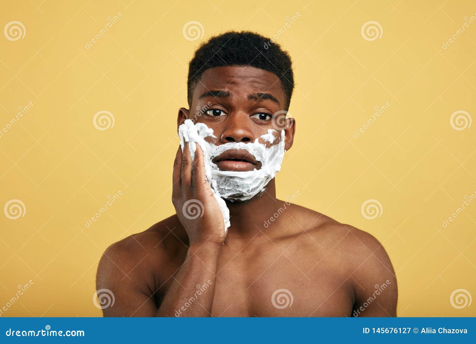 Νέο όμορφο άτομο που έχει τα προβλήματα με το δέρμα κατά τη διάρκεια του ξυρίσματος της γενειάδας του