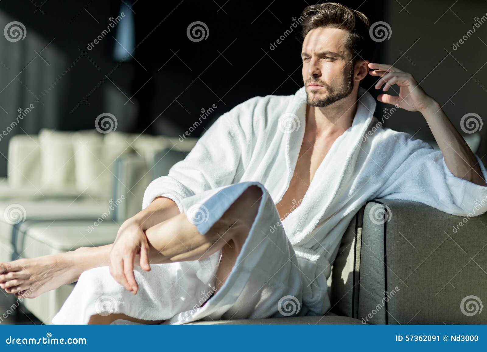 Νέο, όμορφο άτομο το πρωί που σκέφτεται καθμένος σε ένα ρ