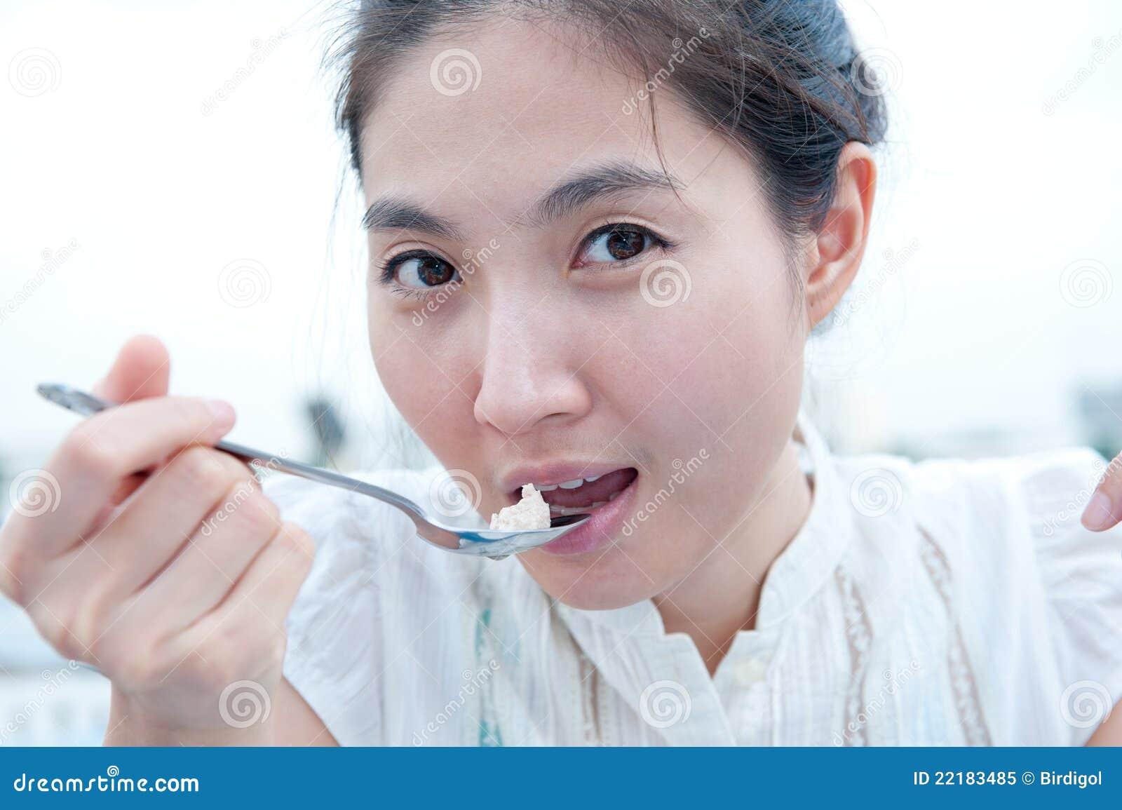 Νέο όμορφο ασιατικό κορίτσι που τρώει τα τρόφιμα (εκλεκτική εστίαση)