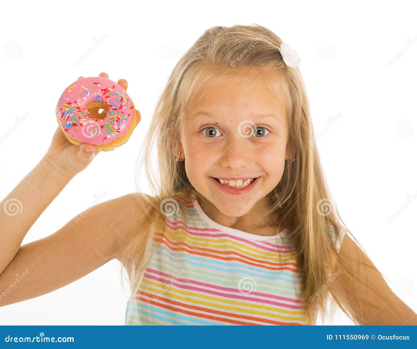 Νέο όμορφο ευτυχές και συγκινημένο ξανθό κορίτσι 8 ή 9 χρονών που κρατά doughnut την έρημο σε ετοιμότητα της που φαίνεται spastic