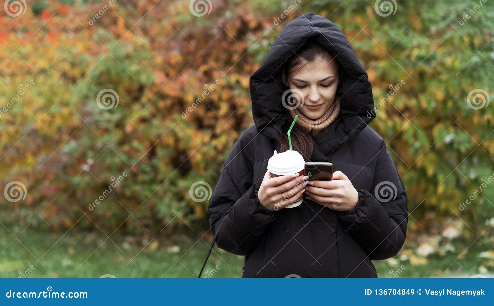 Νέο όμορφο κορίτσι που χρησιμοποιεί το smartphone σε ένα πάρκο φθινοπώρου