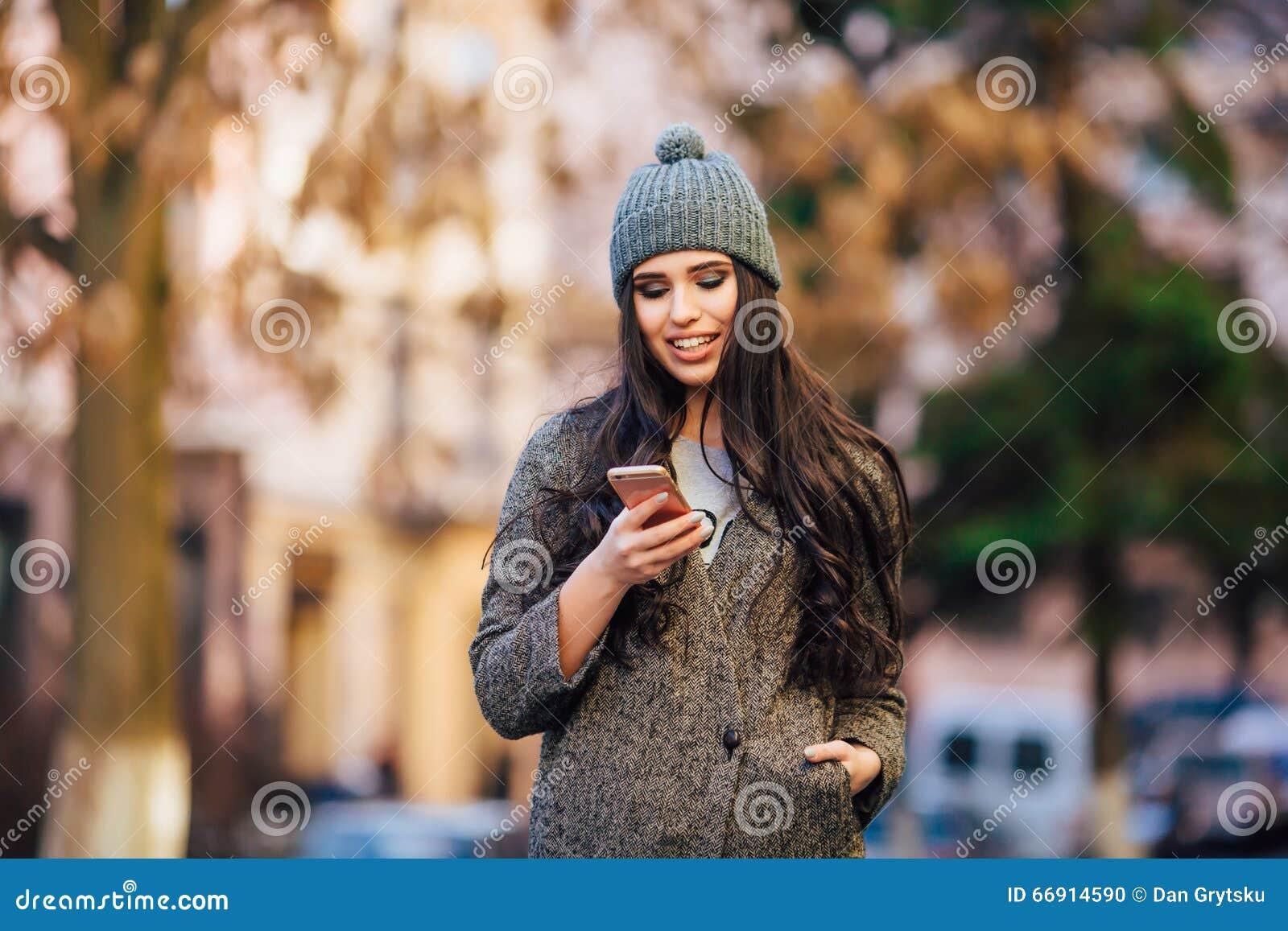 Νέο όμορφο περιστασιακό κοριτσιών στο τηλέφωνο κυττάρων της στην οδό πόλεων άνοιξη
