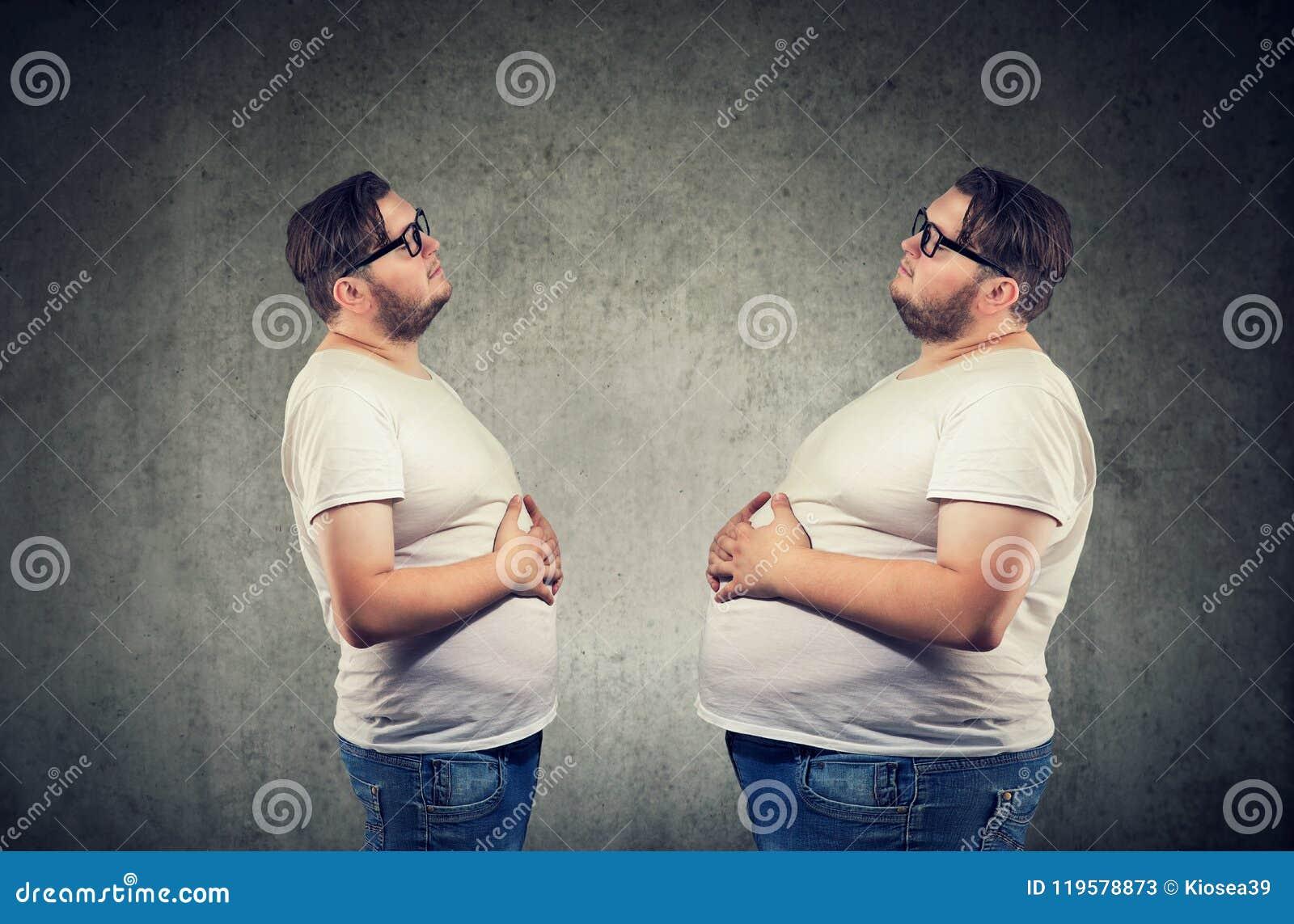 Νέο chubby άτομο που εξετάζει το λίπος ο ίδιος που αισθάνεται φουσκωμένο