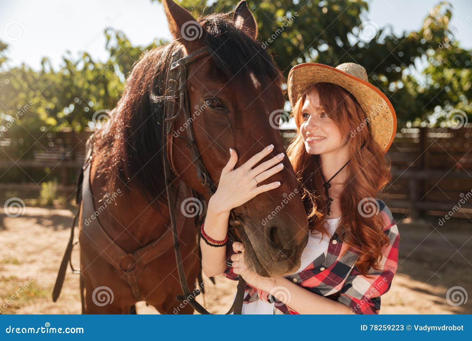 Νέο cowgirl που παίρνει την προσοχή και που αγκαλιάζει το άλογό της στο αγρόκτημα